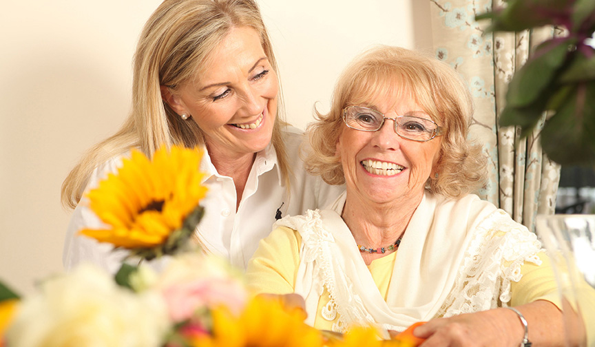 A Cherry Wood Grange resident smiles with a staff member