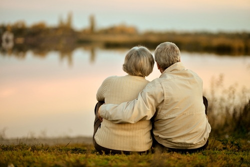 An older couple watch the sunset