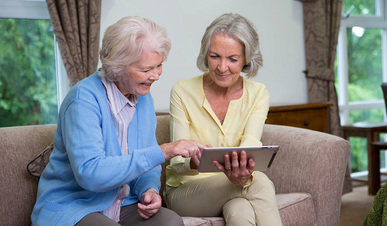 Two residents are sitting on a sofa looking at an iPad